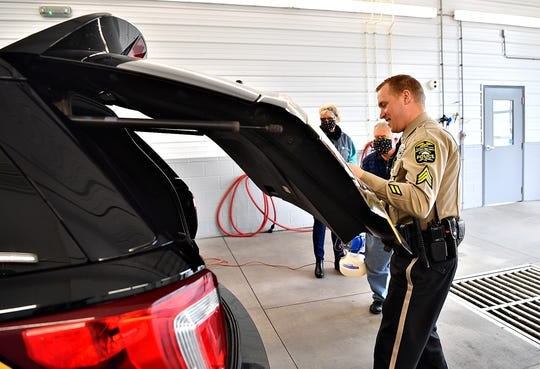 From front, Northern York County Regional Police Sgt. Cody Becker opens the tailgate of his vehicle for John Patterson and Jane Bailey, of Bailey Coach, to disinfect free of charge in Jackson Township, Tuesday, April 7, 2020. Dawn J. Sagert photo