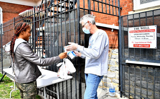 Volunteer Ron Oelrich, right, of Manchester Township, hands supplies, including baby formula, to Jay Dodd, of York City, at The WELL – Food Pantry at Union Lutheran Church in York City, Tuesday, April 7, 2020. The pantry is open 9:30 to 11:30 a.m. Tuesdays, Wednesdays and Thursdays and 8:30 to 10:30 a.m. the second Saturday of the month. Dawn J. Sagert photo