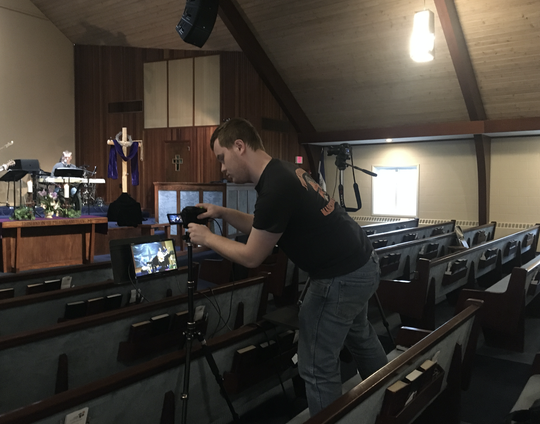 Caleb West, part of the volunteer tech team at York Alliance Church, setting up the live broadcast.