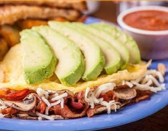 The Racy Tracy, a signature omelet from the Squeeze In restaurants, features bacon, mushrooms, jack cheese and a spray of avocados.