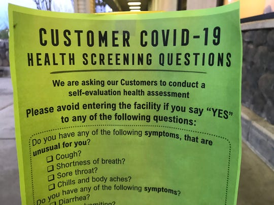 A notice outside Safeway on East Cypress Avenue on Tuesday, April 7, 2020, asks shoppers to stay away from the store if they show these COVID-19 symptoms.