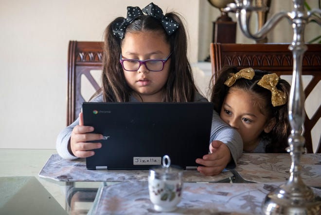 Jizelle Picazo, left, takes a break from school and work and to Cool Math Games on her computer as her sister Jazlyn Carolina Picazo, watches.