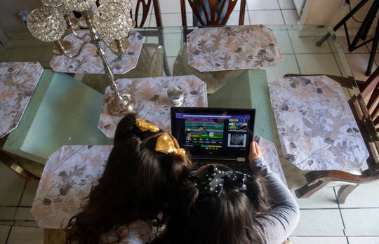 Jizelle Picazo, left, plays Cool Math Games on her computer as her sister Jazlyn Carolina Picazo, watches. The Picazo family is just one of thousands of families getting used to distance learning amid the school closures in Monterey County for the remainder of the 2019-2020 school year. This comes in an attempt to reduce the spread of COVID-19.