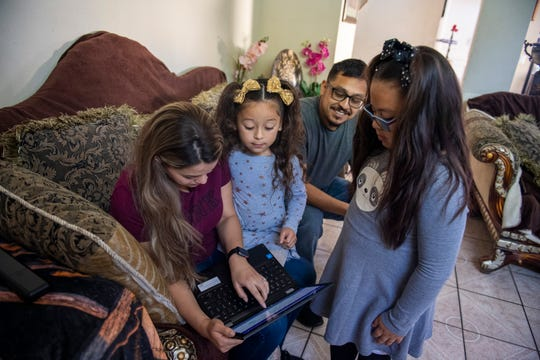 Rosa Picazo, left, helps her daughter solve a problem for her homework as her family Jazlyn Carolina Picazo, middle, Javier Picazo and Jizelle Picazo watch. Distance learning is part of the new normal for thousands of families due to the school closures in Monterey County for the remainder of the 2019-2020 school year.