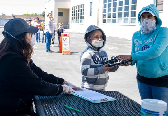 A young boy and his mother sign out a chrome book during the tech distribution at Sherwood Elementary School on Thursday, April 2, 2020.