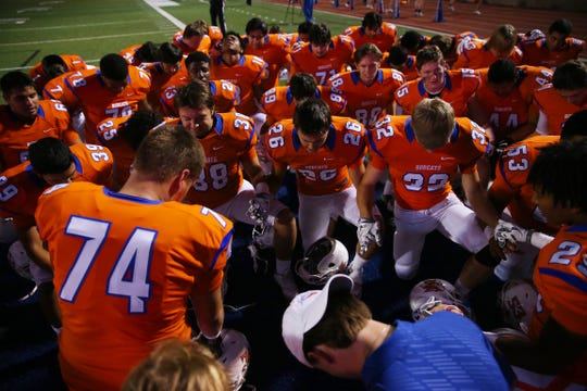 Braxton Webb (74) and the Central High School takes a knee in prayer before a 2015 game against Midland High at San Angelo Stadium.