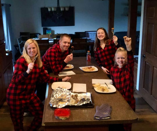 Betsy, Joe, Halle and Hayden Weber eat dinner together during their first family theme dinner, wearing their matching Christmas pajamas.