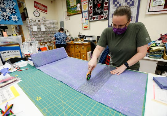 Holly Fletcher cuts fabric for face mask kits at Merrily We Quilt Along on Tuesday, April 7, 2020.