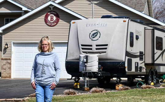 Kristin Brandt stands outside her home Tuesday, April 7, 2020. Brant spent a month in the hospital recovering from acute respiratory distress syndrome in 2009, and is taking extra precautions to make sure she does not contract the COVID-19 virus. Her husband Jeremy now lives in a camper in their driveway to avoid transmitting the virus.