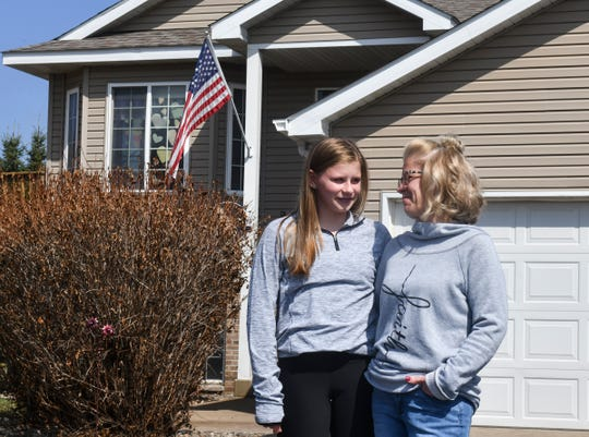 Kristin Brandt smiles at her daughter Bella outside ther home Tuesday, April 7, 2020. Brant spent a month in the hospital recovering from acute respiratory distress syndrome in 2009, and is taking extra precautions to make sure she does not contract the COVID-19 virus.