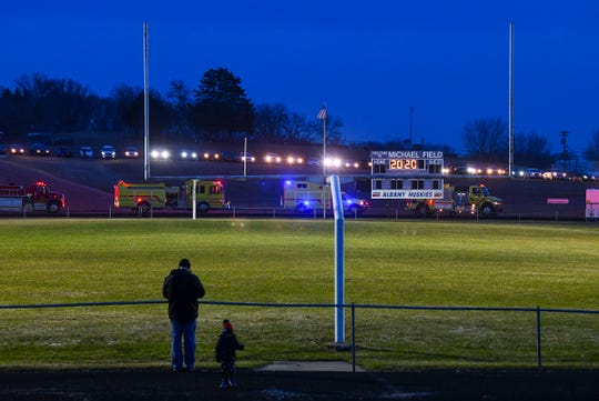 "Activities director Scott Buntje watches with his son as the lights are turned on for 20 minutes and vehicles line a hill near Michael Field as part of the ""BeTheLightMN"" movement to pay tribute to the members of the Class of 2020 Monday night at Albany High School."