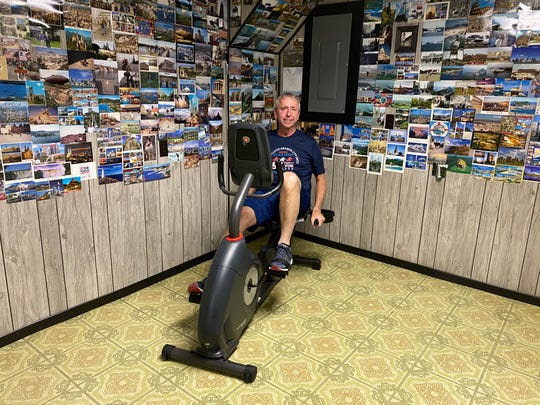 St. Cloud Mayor Dave Kleis rides his new exercise bike in the room he filled with memories of his favorite trips and places of where he wants to go.