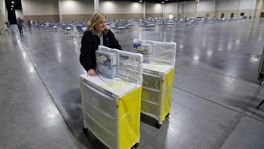 EMT Jan Robinette pushes isolation carts in an area set-up with beds at the Mountain America Expo Center Monday, April 6, 2020, in Sandy, Utah. The State of Utah has contracted with Salt Lake County to use the Mountain America Expo Center as an alternate care site, or hospital overflow. This is not a site for COVID-19 patients. It is simply an overflow site for certain types of care, should the need arise. It will initially be stocked with 250 beds and medical equipment. (AP Photo/Rick Bowmer)