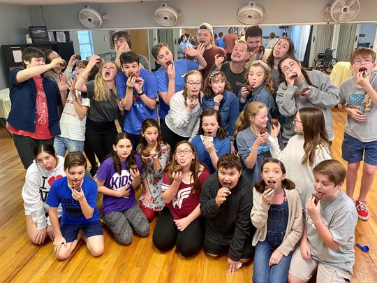 """The Young Actor Theatre cast of """"Matilda"""" eating chocolate cake in a scene from rehearsals."""