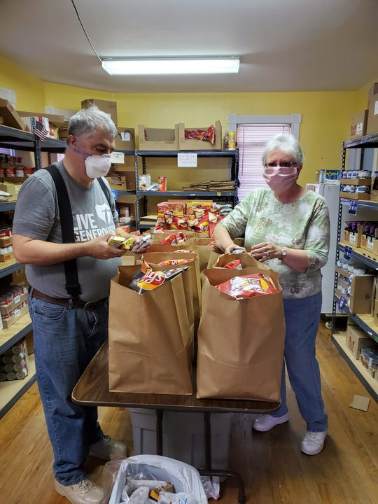 Bill and Jade Mitchell make up grocery bags Tuesday at Help & Hope Ministries in Millville. The nonprofit switched from having clients shop at its Howard Street site to home delivery in March due to the coronavirus. Submitted photo by Chuck Brett