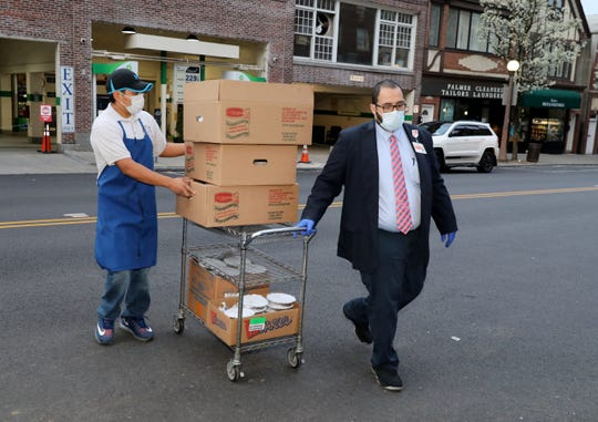 A cart full of 250 meals is wheeled across Palmer Avenue, on its way to the staff at New York Presbyterian Lawrence Hospital in Bronxville, April 7, 2020. The meals, including omelets, bagels, and sandwiches were prepared by the Park Place Bagels 2 and donated by Hero Meals NYC.