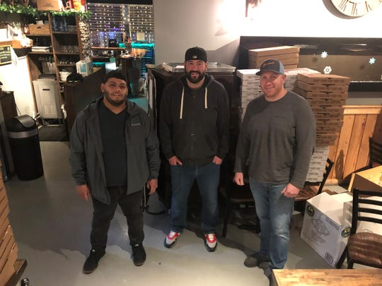 The Norcina owners with their stacks of pizza boxes behind them. Left to right: Erick Carrasco, Milan Dobrilovic and Nick Nuccio.