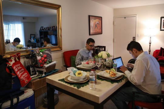 16-year-old twins Ryan and Marco (right) Caba-Acevedo complete work on the computer out of their Newark apartment on Tuesday, April 7. Marco said he thought remote learning would be more difficult, but the classes are currently just reviewing past concepts.