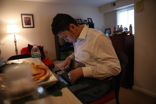 16-year-old Marco Caba-Acevedo completes work on the computer out of a Newark apartment on Tuesday, April 7. In addition to a couple hours of remote classes, he prepares for the SAT and reads books assigned by his mother.