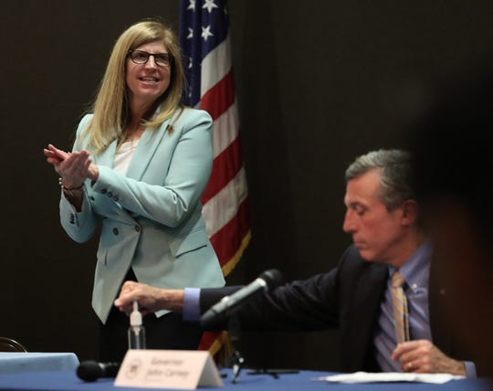 Dr. Karyl Rattay, director of the Delaware Division of Public Health and Gov. John Carney use hand sanitizer after a press briefing on the state's coronavirus situation Tuesday at the Carvel State Office Building.