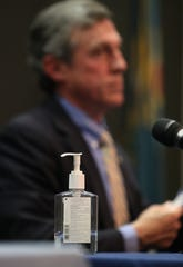 A bottle of hand sanitizer rests next to Gov. John Carney as he and administration officials conduct a press briefing on the state's coronavirus situation Tuesday at the Carvel State Office Building.