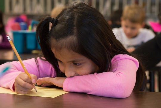 FILE - In this Nov. 26, 2018, file photo, Odalys Tebalan works on an assignment at Fairview Elementary in Carthage, Mo. Millions of children are suddenly learning at home everything from reading and multiplication to literature and calculus as a result of school closures prompted by the global coronavirus pandemic. Many parents are trying to guide their children through assignments, but many face the challenge of English comprehension.