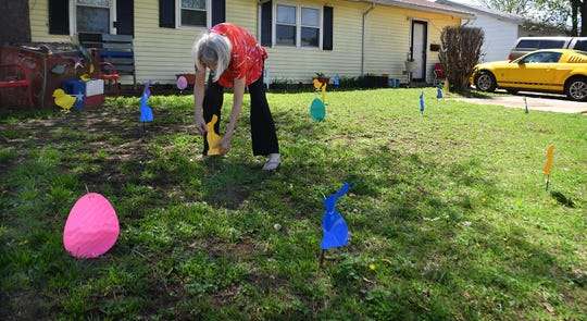 Julie Coley straightens one of the bunnies in her front yard which she has made into a virtual Easter egg hunt for small children to spot items with their parents from their cars.