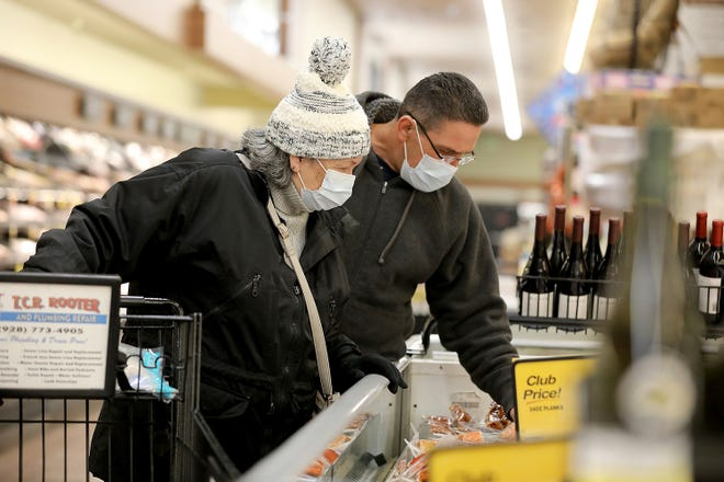 Shoppers like Hector Molina, right, helps his mother Gertrude Moore don wear protective masks and gloves as they visit a grocery store. Many shoppers are trying to stay safe during the COVID-19 pandemic and wonder just how safe their food is.