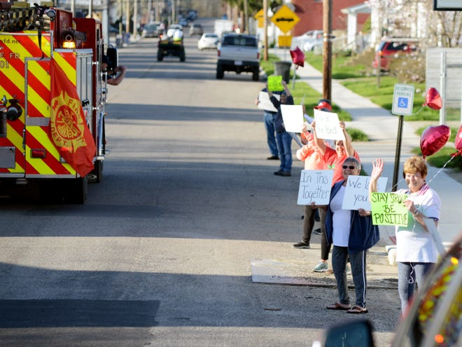 Residents held signs on Main Street in support of the Roseville Fire Department during a parade on Monday.
