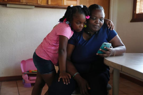 Willie Mae Daniels spends time looking at videos with her granddaughter, Karyah Davis,6, after being laid off from her job as a food service cashier at the University of Miami on March 17 as the university joins in the effort to fight the coronavirus on March 26, 2020, in Miami, Florida.
