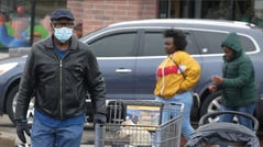 A man covers his face with a mask while shopping at Pick 'N Save near 60th and Capitol, Saturday, March 29,2020. The neighborhood is located in a hot spot for coronavirus in Milwaukee according to a map by Milwaukee County Office of Emergency Management.