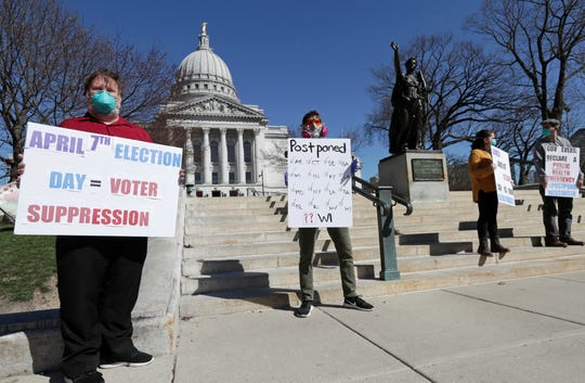 A group with C.O.V.I.D., Citizens Outraged Voters in Danger, protest wearing masks outside the State Capitol during a special session regarding the spring election in Madison, Wis., Saturday, April 4, 2020.