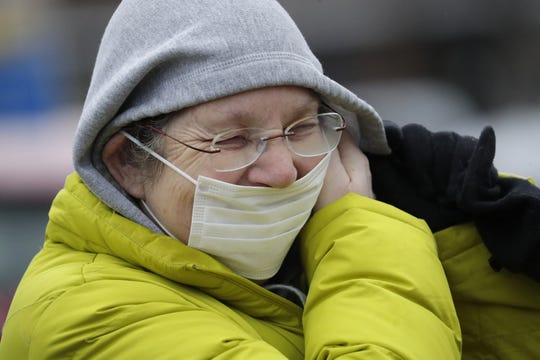 Neenah resident Carol Clark puts on a protective mask before entering the former Neenah Shopko store to vote Tuesday. The building served as Neenah's sole polling place.