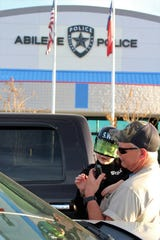 Dakota Helmick holds his son John Wayne Helmick, 6, who is dressed as a SWAT member. They were in the parking lot of the Abilene Police Department on Tuesday evening, when a come-and-go prayer event was held. The youngster is a kindergartener at Lee Elementary School.