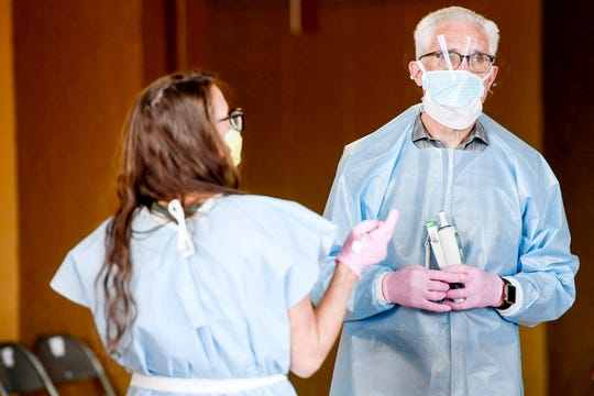 Medical professionals wait to screen people as they are checked into the Harrah's Cherokee Center April 8, 2020, in the midst of the coronavirus pandemic.