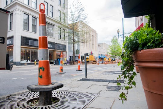 A cone sits on top of a stump along Haywood Street as a crew works on the Haywood Streetscape Improvement project on April 8, 2020. The project includes road resurfacing, fixing stormwater issues and sidewalk repairs.