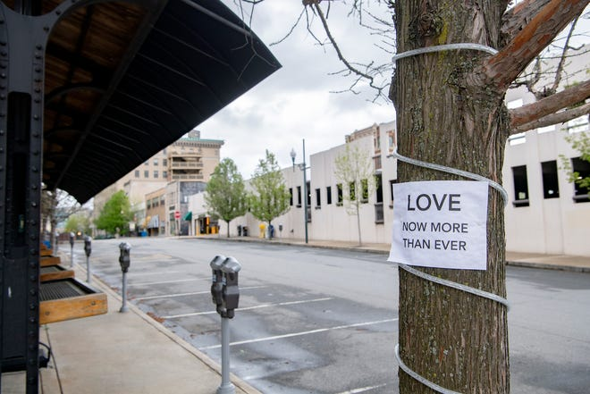 "Paper signs reading ""love now more than ever"" were posted around a deserted downtown Asheville on April 8, 2020."