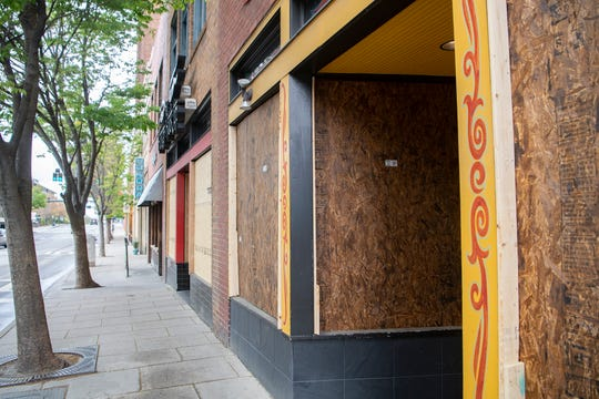 A line of businesses on Patton Avenue  in downtown Asheville had their doors and windows covered in plywood following their closure to slow the spread of coronavirus on April 8, 2020.