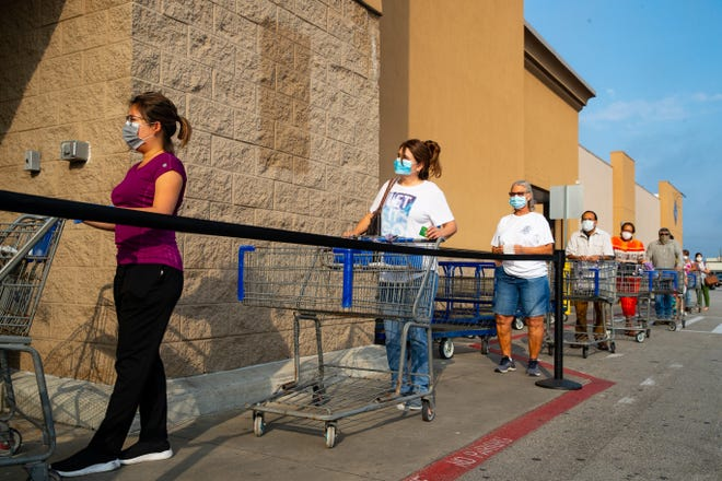 Masked shoppers wait in line at Sam's Club.