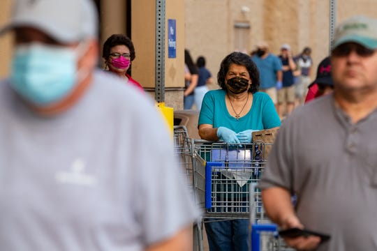 People wear masks as they wait inline to enter Sam's Club on Wednesday, April 8, 2020.