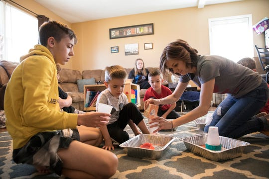 Sondra Dettwiller adds more baking soda to a home-made volcano, so it will erupt during a science project that several of the kids participate in. Dettwiller tries to keep everyone on a consistent schedule due to having eight children ranging from five to 14 in their home.