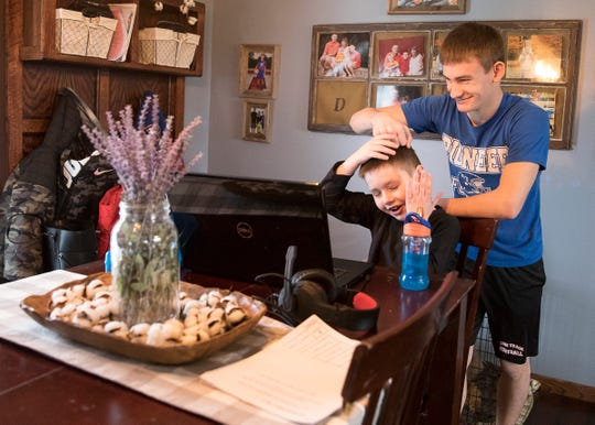 Gage Dyke has some fun with his brother while he works on a homework assignment. Gage helps his brother start his homework which is later checked by his mother.