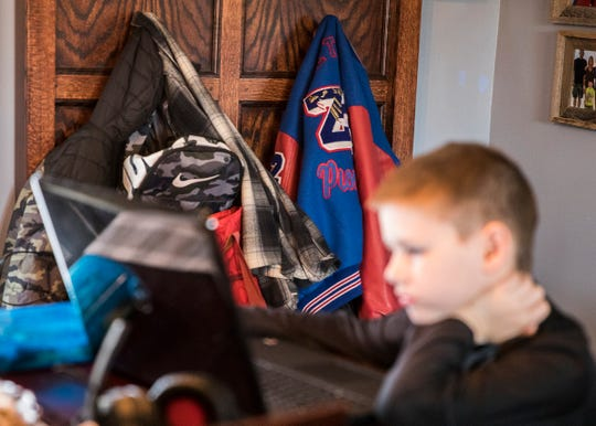 Bookbags and a lettermen jacket hang on their hooks as Archer works on a computer assignment. The normal school items have not moved since homeschooling has begun.