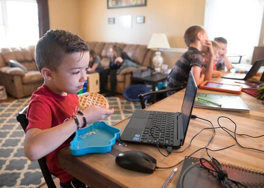 Ace Dettwiller eats his breakfast as he talks with his classmates as he and his siblings start the school day at home due to the  coronavirus epidemic and keeping everyone in home school.