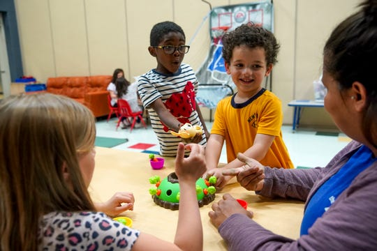 Daivion Bryant, left, and Nikolas Fields, center, play a game with area coordinator Ileana Diaz at Clarksville YMCA in Clarksville, Tenn., on Tuesday, April 7, 2020.