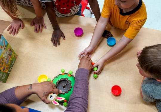 Kids play a game with their teacher Ileana Diaz during a play period of daycare at Clarksville YMCA in Clarksville, Tenn., on Tuesday, April 7, 2020.