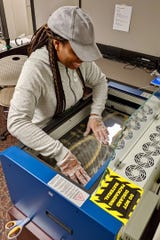 APSU student Ciara Grandberry places plastic for face shields into a laser printer at the APSU GIS Center on April 7, 2020.