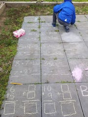 Kiera Johnson's son is doing his math homework with chalk outside.