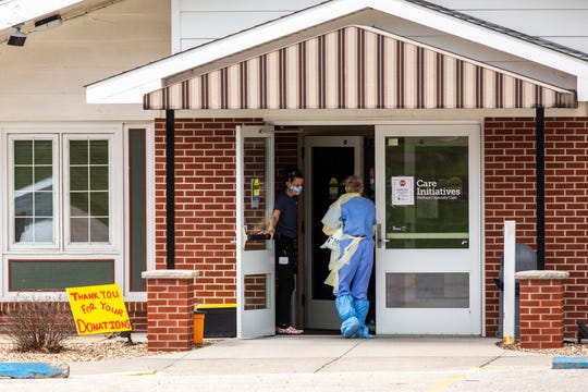 Heritage Specialty Care employees dressed in personal protective equipment (PPE) arrive at the building, Wednesday, April 8, 2020, at 200 Clive Drive SW in Cedar Rapids, Iowa.