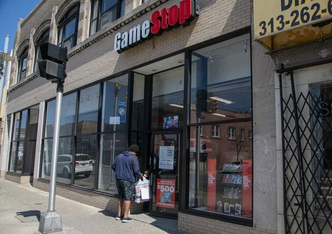 Leondre Leonard, 33, of Warren is greeted by a GameStop employee in Hamtramck to pick up a PS4 PlayStation he ordered online. Leonard, who said he was really bored, mentioned this was the only time he has gone out. GameStop is open in spite of  a stay at home mandate due to the spread of the Novel Coronavirus.